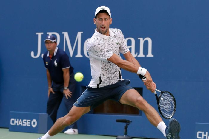A male tennis player prepares to hit a two handed backhand shot on the run with his legs wide apart