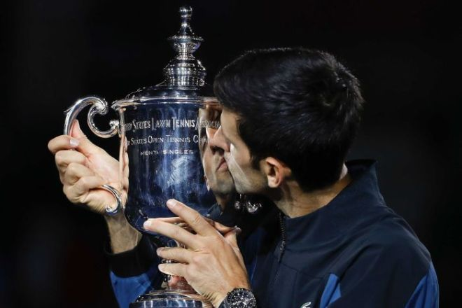 Novak Djokovic kisses a large silver cup.