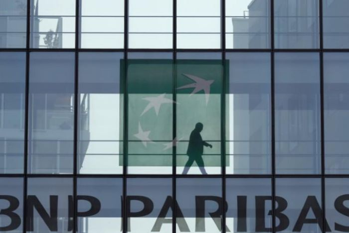 A man is seen in silhouette as he walks behind the BNP Paribas logo in a building in Issy-les-Moulineaux, near Paris, France.