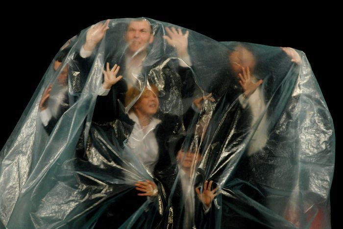 A small group of people wearing suits, inside a thick plastic bag, trying to push through it, looking worried.