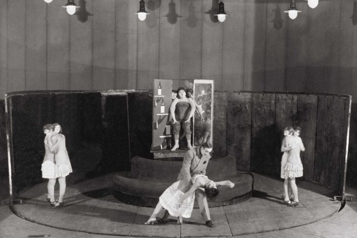 Black and white image of a stage with performers including women embracing, and a man and woman dancing at centre.