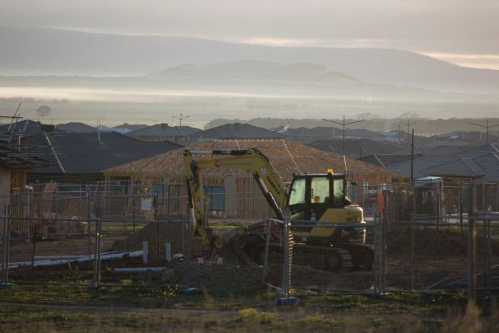 A digger on the construction site at a new housing estate in Mickleham, Victoria at sunrise.
