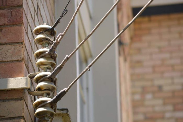 An set of electricity wires are attached to a cobwebbed metal rod mounted on the side of a brick building.