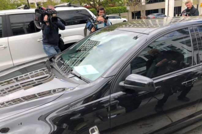 Unmarked Australian Federal Police car drives away from Home Affairs office surrounded by media