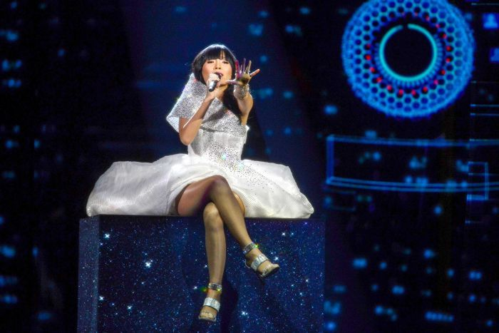 Singer Dami Im seated on a tall block while wearing a sparkly silver gown