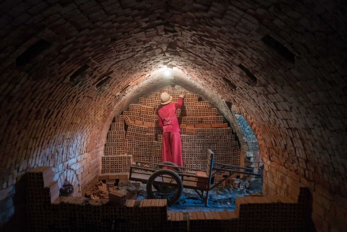 A woman removes bricks from inside a kiln in Cambodia.