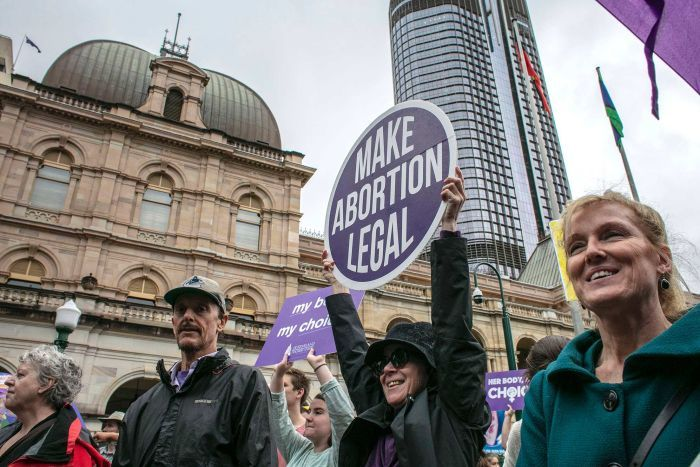 People are seen attending the March together for Choice rally in Brisbane.