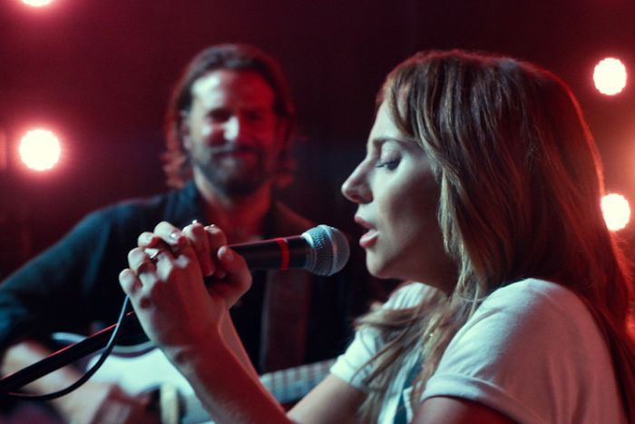 Lady Gaga holding microphone and singing into it, Bradley Cooper in background watching, red stage lighting.