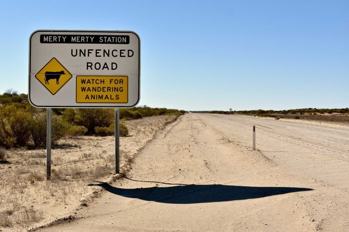 A large sign which marks the boundary of Merty Merty Station sits on the side of a white dirt road which has been graded.