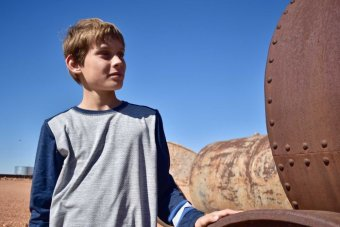 A young boy stands next to a rusted metal farming implement against a blue sky