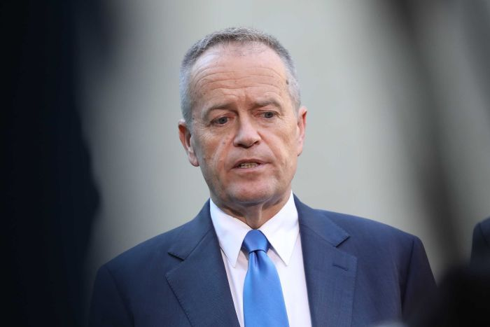 Mr Shorten looks down while mid sentence. He's wearing a blue tie and suit.