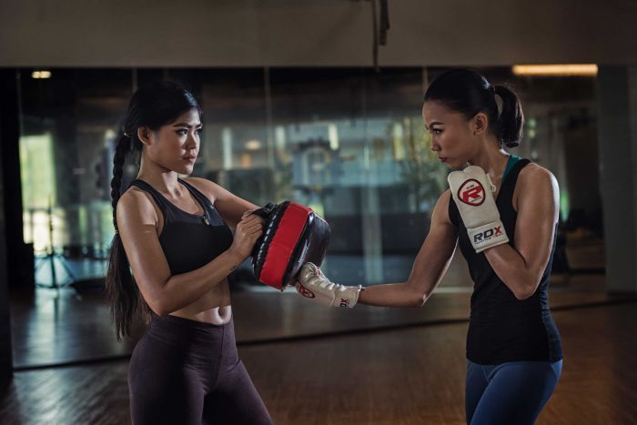 Two women demonstrate practice sparring at a self defence class.