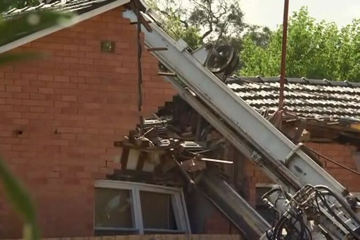 The crane boom rests on the damaged section of the house.