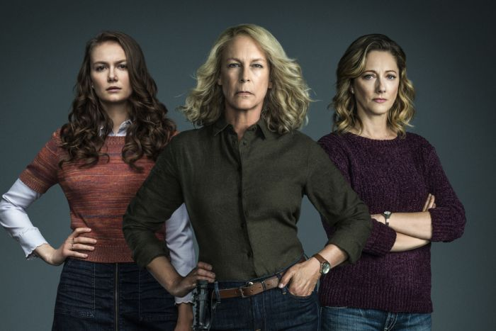 Three women stand with hands on hips or arms folded, and hair out, with solid background behind.