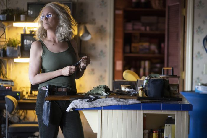 Jamie Lee Curtis with wavy shoulder-length hair in army-green tank top and black jeans, wearing tool belt with massive knife.