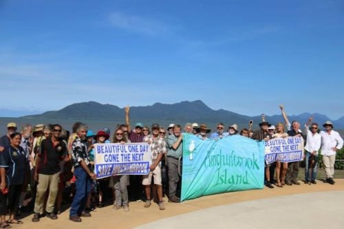 A group of opponents to the proposed lease on the island hold banners and signs