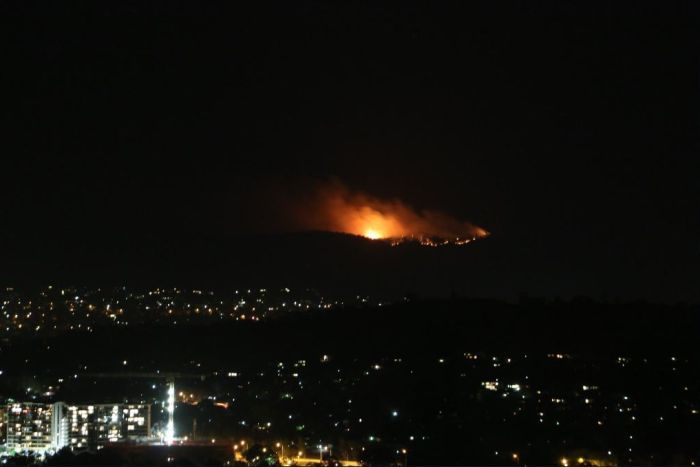 View form a hill overlooking Canberra at night, with blazes burning on hills in distance.