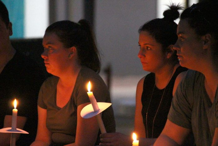 Mourners hold candles at the vigil for the allegedly murdered woman.
