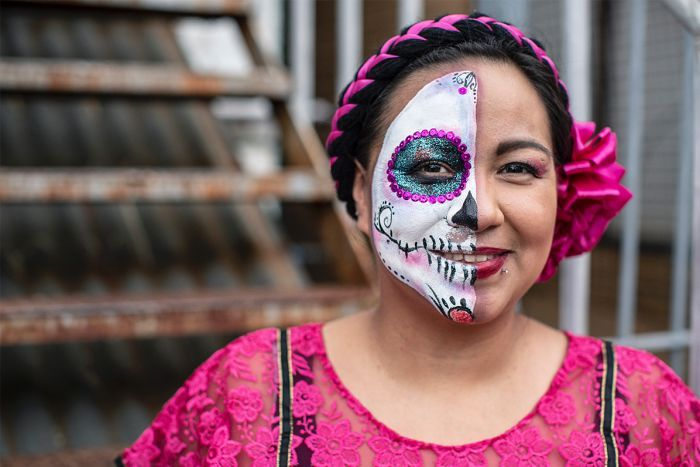 Rosa Cienfuegos stand outside wearing Day of the Dead skeleton make-up on half her face.
