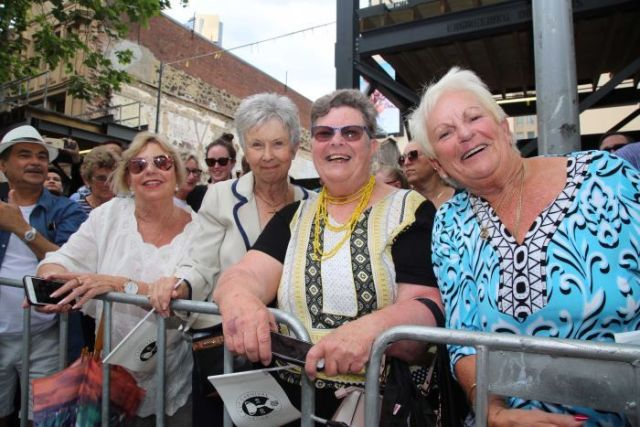 Four women standing behind barrier, staring and smiling at camera.