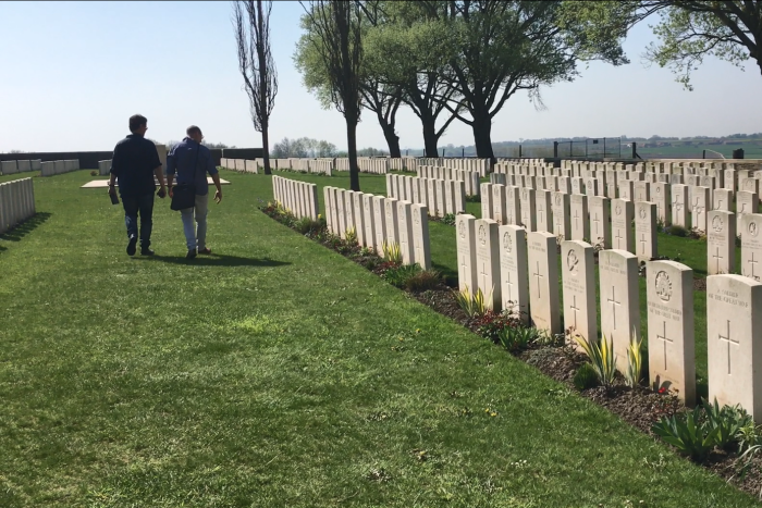 Two men walking alongside white headstones in a war cemetary in France.