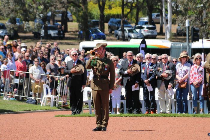 A bugler at the Remembrance Day National Ceremony in Canberra, standing in front of a crowd.