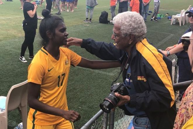 Young Matildas player Shay Evans embraces former Socceroo and Indigenous football champion John Moriarty