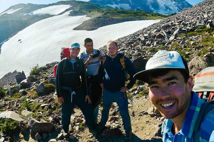 A man smiles as he takes a picture of himself with three friends atop a mountain.