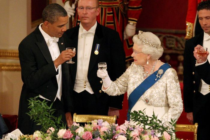 Barack Obama - dressed in tuxedo - and the Queen - in a jewel-adorned dress - look at each other, holding glasses in a toast.