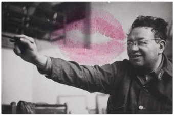 An black and white photo of Diego Rivera painting is embellished with the red lipstick mark left by Frida Kahlo's kiss.