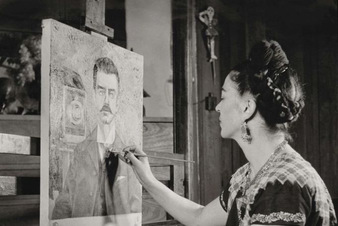 Frida Kahlo works on a portait of her father, Guillermo. She's seen wearing her traditional dress and hair tied up in braids.