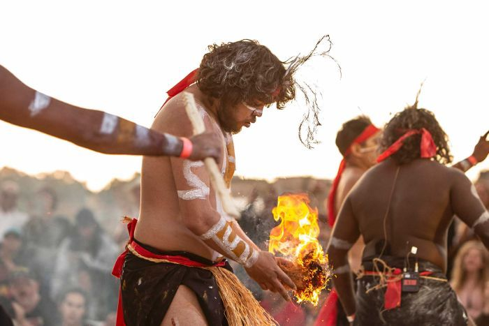 Colour side on photo of Ashley Ruska of dance group Nunukul Yuggera holding small fire during performance at Dance Rites 2018.