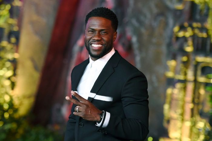 Kevin Hart, wearing a suit, smiles and holds up two fingers as he poses for the camera while arriving at a movie premiere.