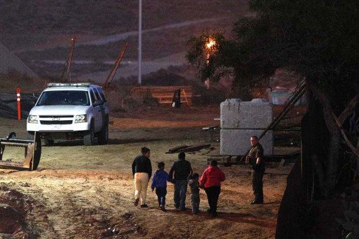 Three adults and two children walk in a line holding hands, as a uniformed man looks on, at night, near a large vehicle