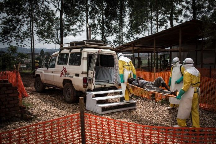 Three people in Ebola scrubs carry a patient on a stretched into an ambulance.