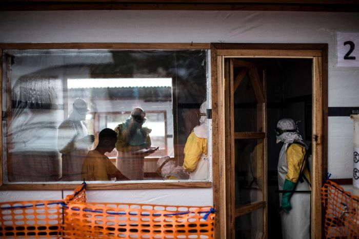 People wearing protective clothing from Ebola discussing treatment.