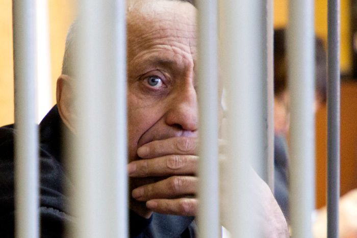 A man with his hand on his mouth, obscured by prison bars.