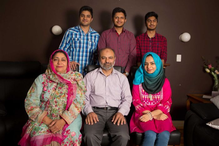 Umer, Danial and Ali stand in front of their mum, dad and sister who are sitting on chairs in their living room.