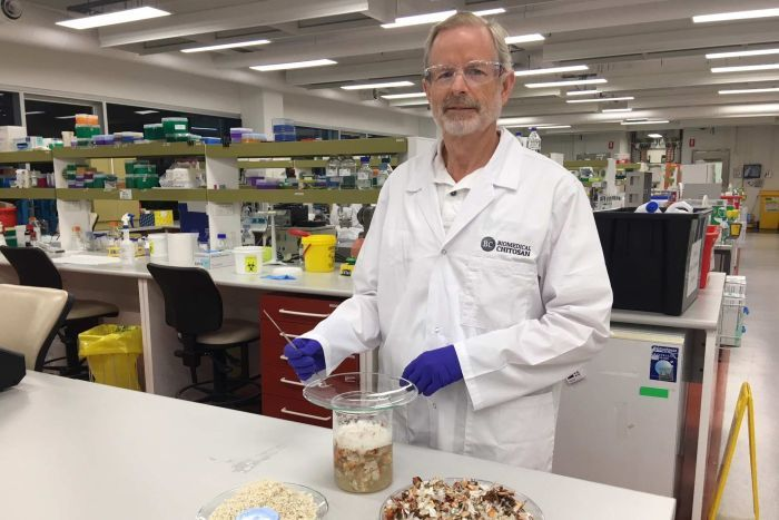 David Hewitt standing in a lab with bowl of prawn shells.