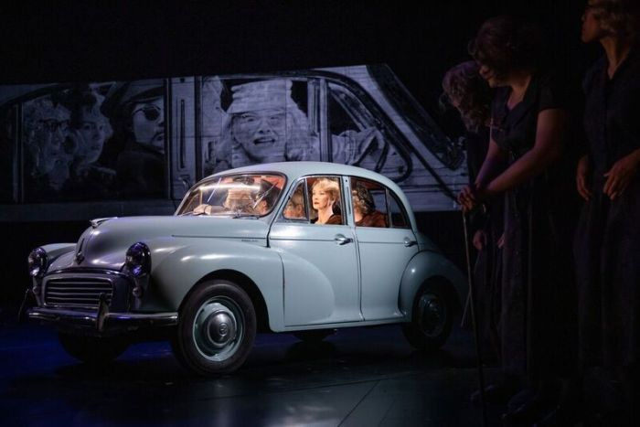 A blue car on a stage with actors inside