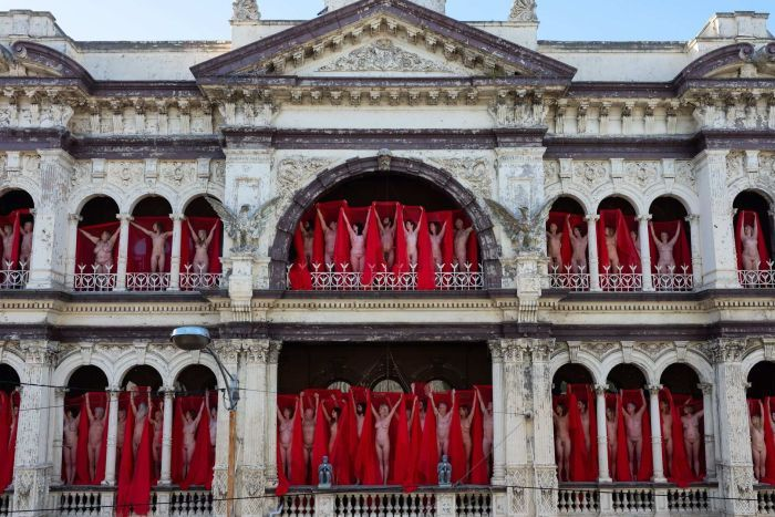 Naked people standing on balconies draped in red veils.