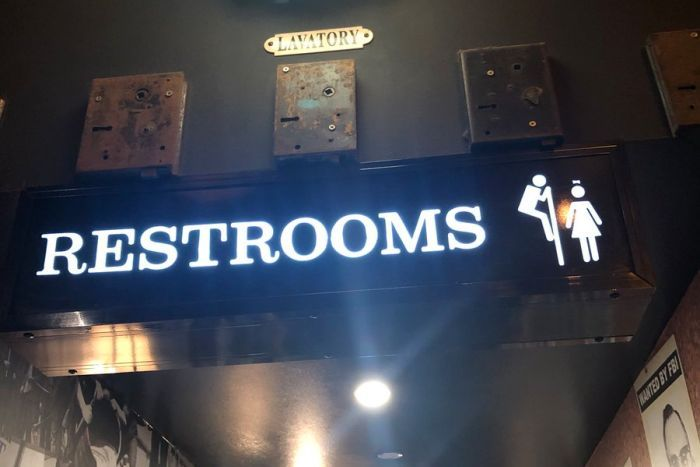 A photo of a sign at Melbourne bar Father's Office depicting a man appearing to looking at a women over a cubicle wall.