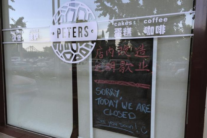 Julia and Kevin Garratt owned coffee shop in China with sorry we are closed sign