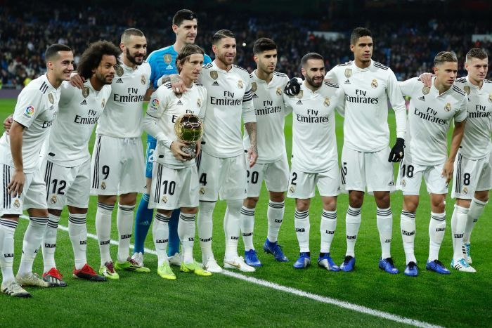 Real Madrid's Luka Modric holds his Ballon d'Or (Golden Ball) award with his teammates.