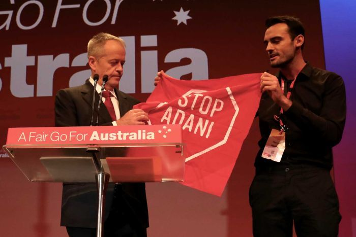 "Mr Shorten is holding the banner the protester is brandishing, which says ""Stop Adani"""