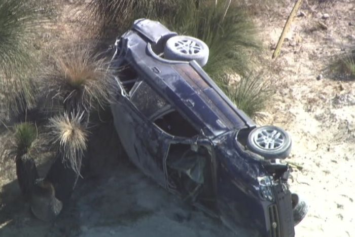 An aerial shot of a dark blue car on its side on a sandy road.