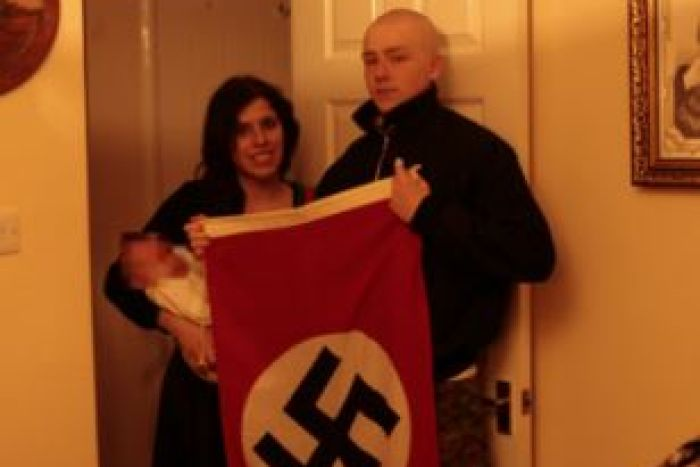 Claudia Patatas holds the pair's son while Adam Thomas holds a swastika flag.