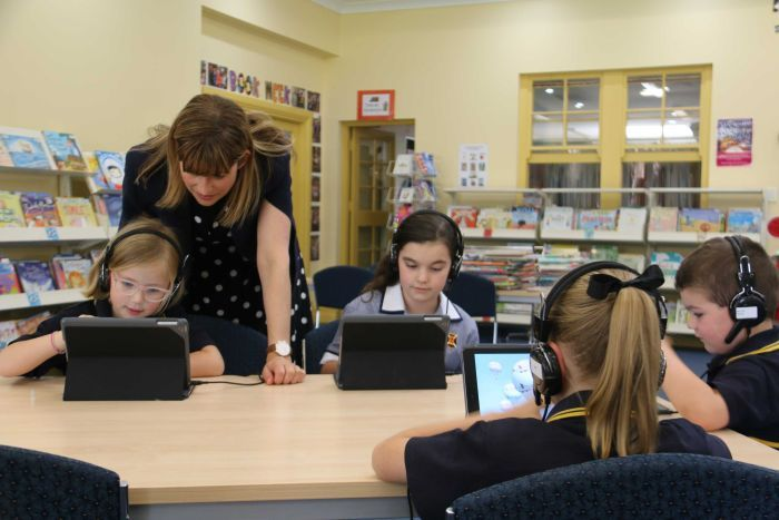 Primary school students use laptops in the library.
