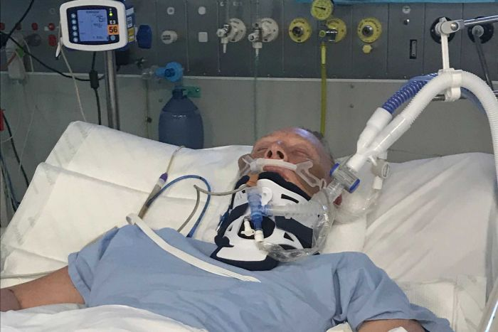 A woman lying in a hospital bed in a coma. She has multiple tubes attached to her and is in a neck brace.