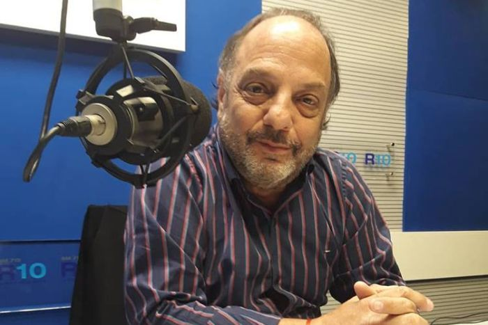 A man sitting in a radio studio with a microphone near his face.